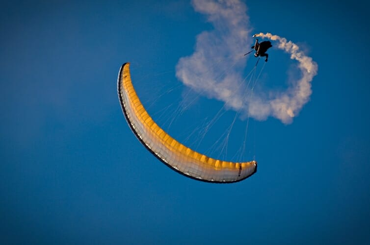 paragliding doing tricks with smoke