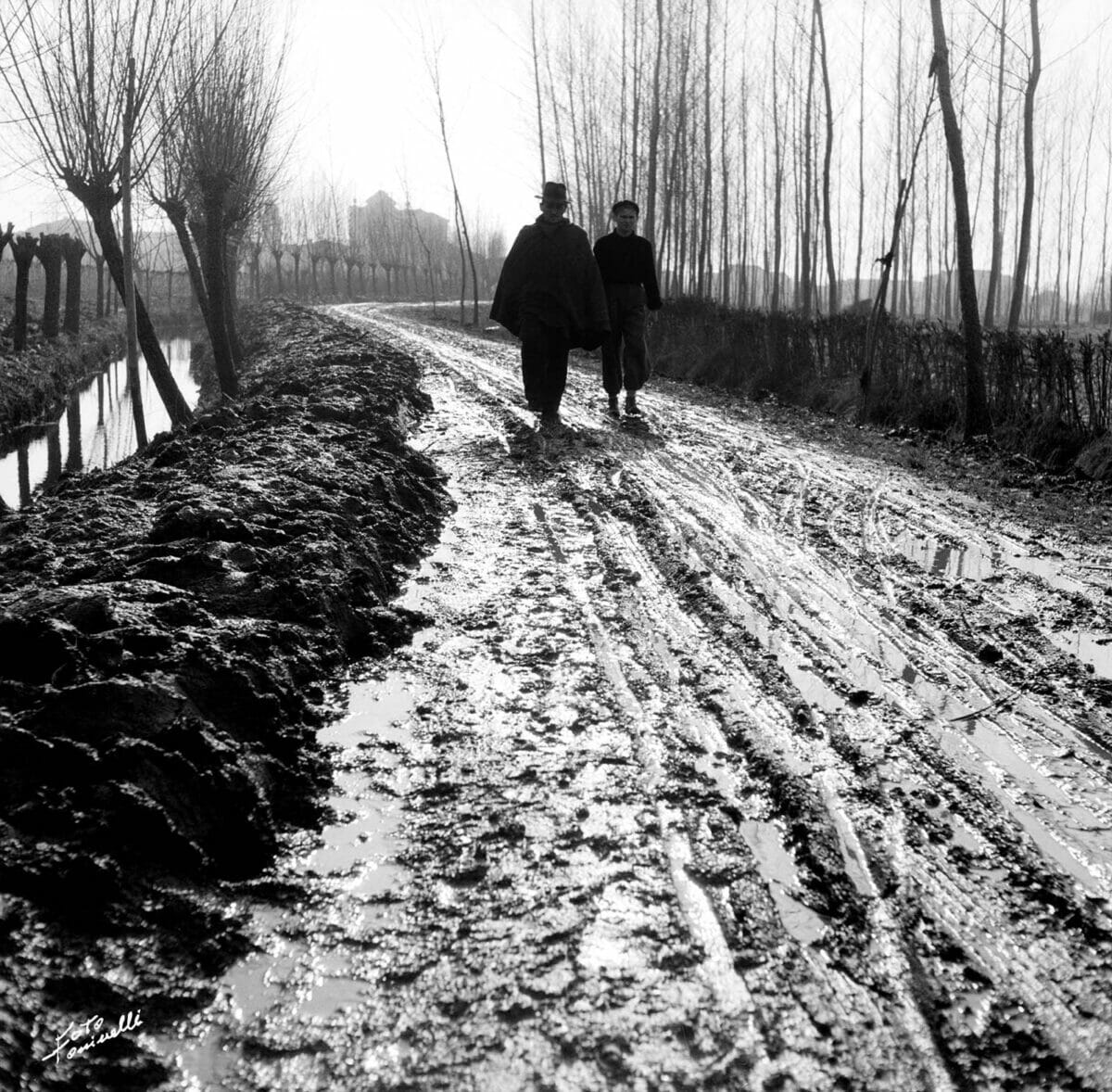 people walking on a muddy road