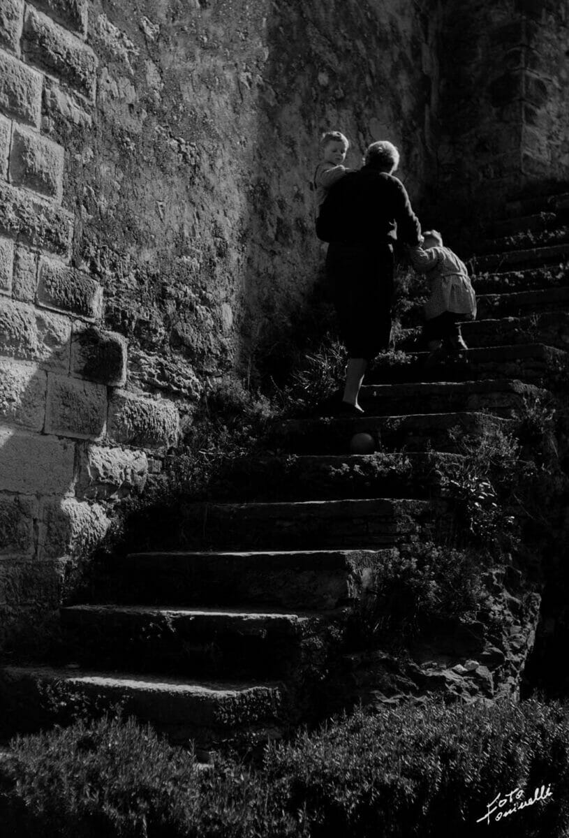 elder woman with children on a stair